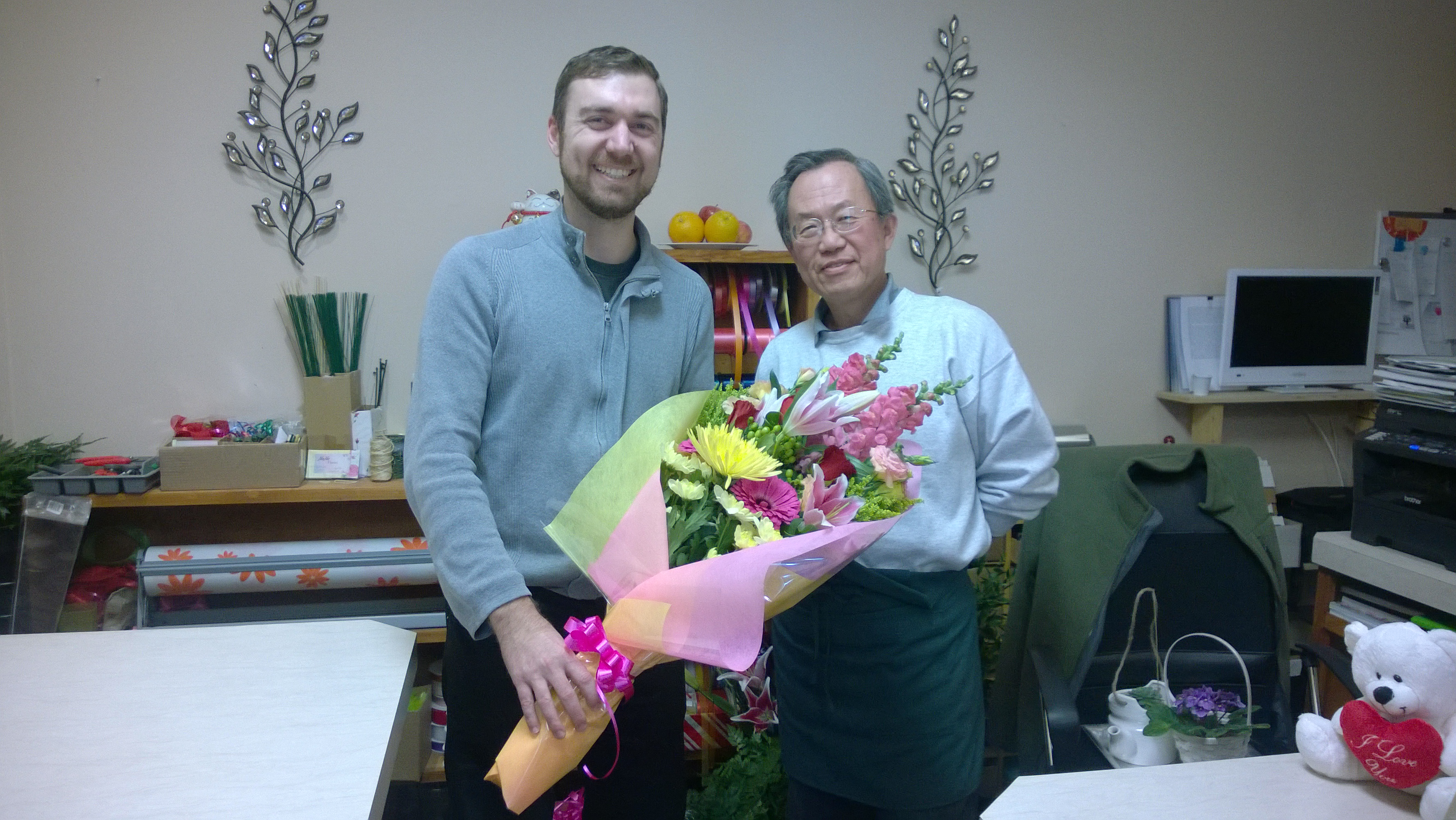 Mark Rullo with Shiro, the owner of NaNa Florist, buying an early Valentine's Day gift for his wife, Stephanie.